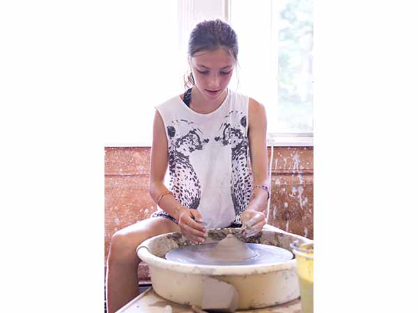 Young girl spinning pottery on the wheel in pottery studio at summer camp
