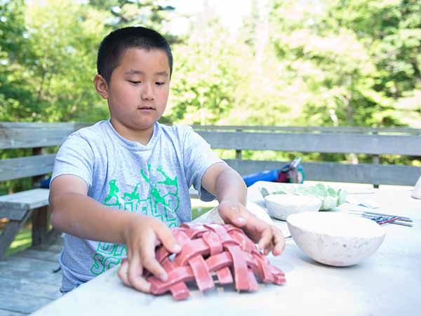 Child weaving basket made of clay in the pottery studio at summer camp