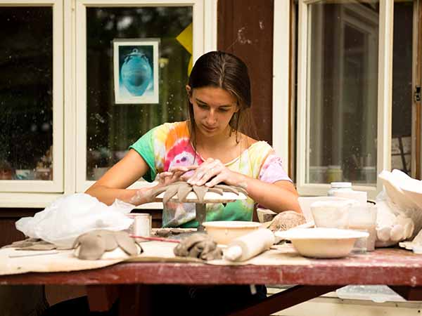 Teen creating platter out of clay in the pottery program at camp