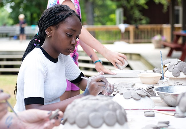 African American girl working with clay pottery at summer camp