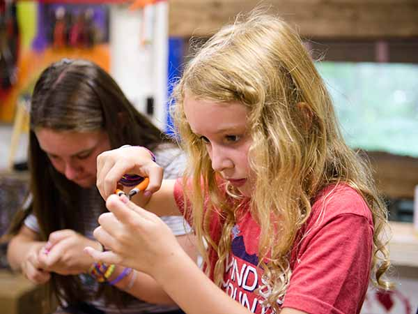 Young girl making jewelery with beads in art program at summer camp in New Hampshire