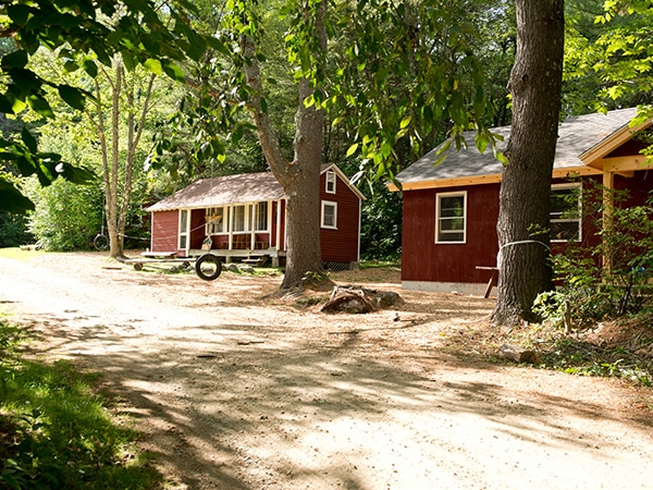 Wonderful Red Cabins For Youth Campers With Tire Swing At Summer Camp