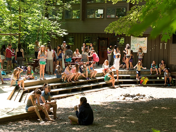Young female campers gathered at treehouse cabins in at summer camp