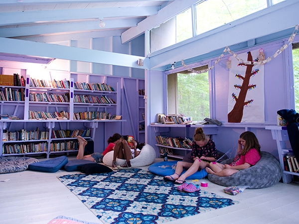 Library at summer camp with young girls reading books