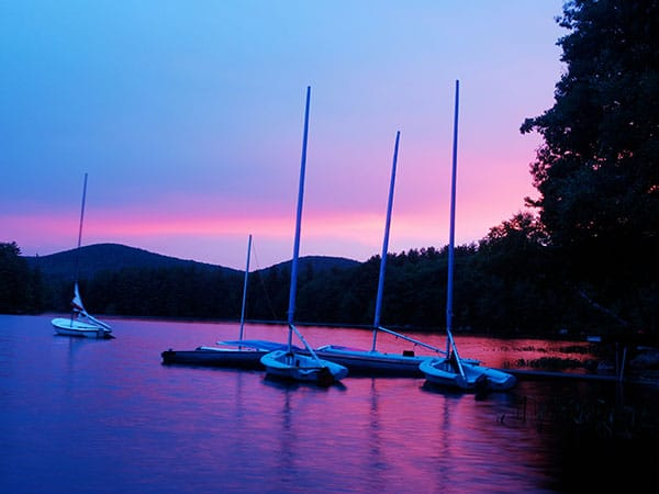 Beautiful pink and purple skies during sunset on the lake with mountain background