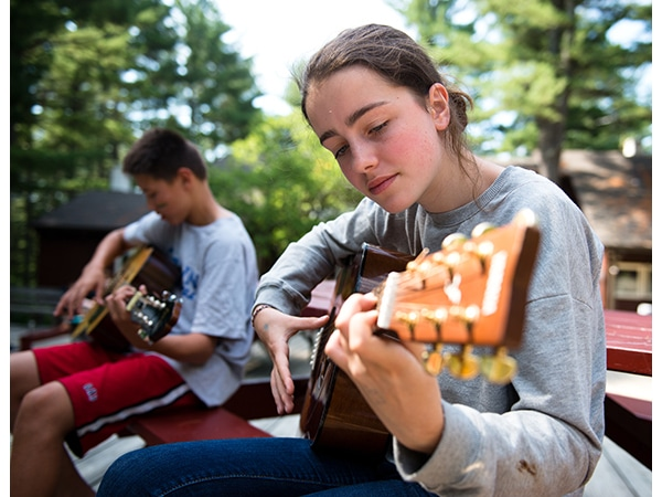 Girl playing guitar during music lesson at summer camp in New Hampshire