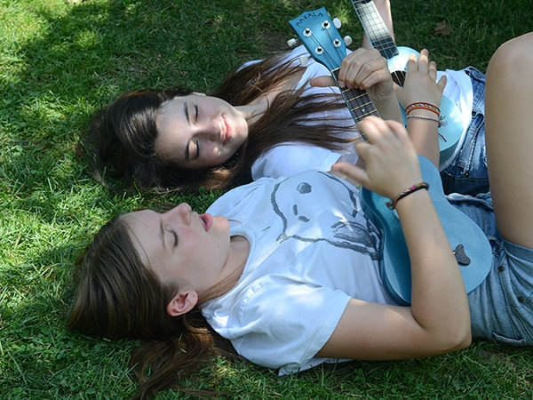 Friends playing ukelele together in the grass