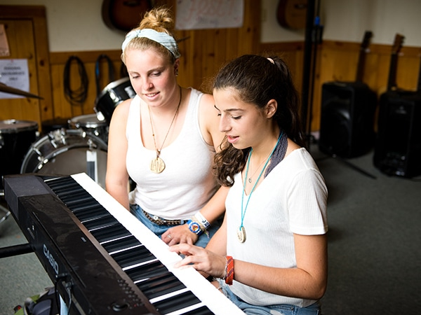 Girl and counselor playing piano during music lesson at camp