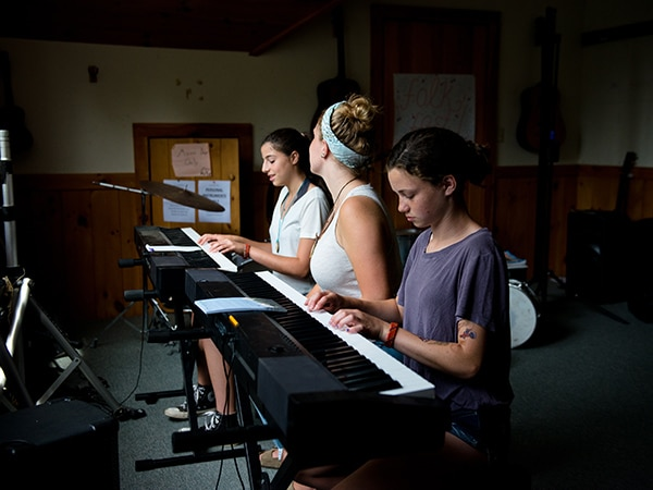 Girls learning the keyboard piano with female musician instructor