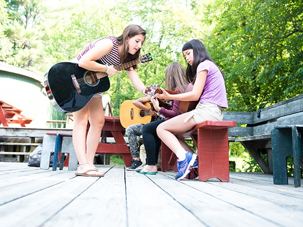 Female musician counselor teaching guitar to young camper