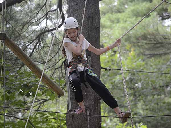 Girl walking the tight rope on the ropes course at summer camp