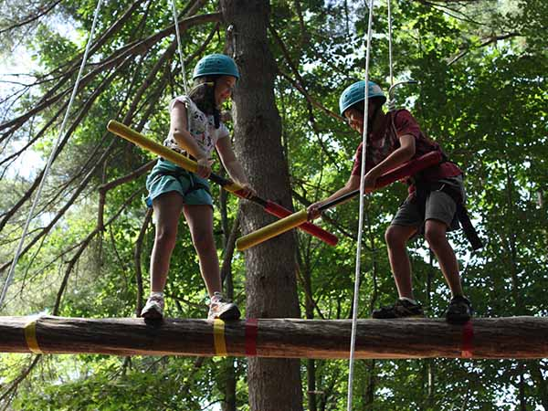 Kids challenge eachother on the high ropes course at summer camp