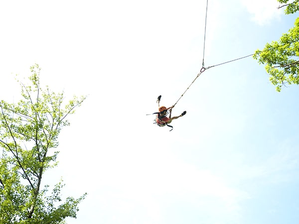Girl on giant rope swing at summer camp