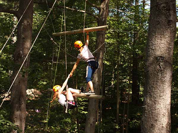 Child helping another camper climb ladder on the ropes course