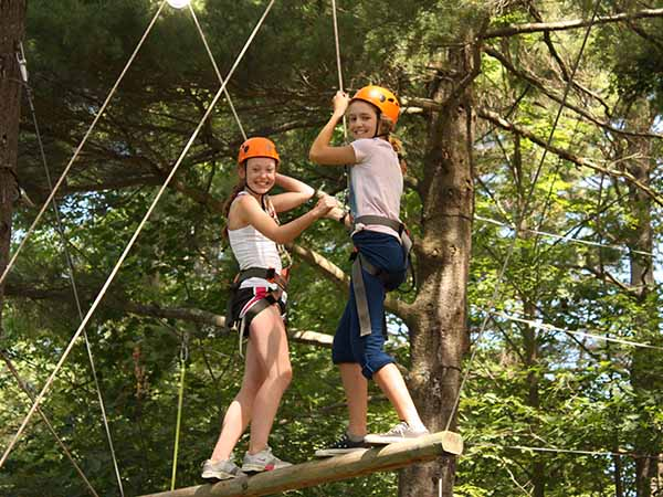 Young girls working together on the outdoor climbing and ropes course