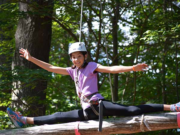 Teen does gymnastics on the balance beam on the outdoor ropes course