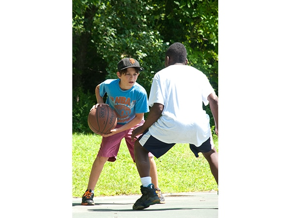 Youth campers playing basketball at summer camp