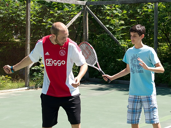 International camp counselor instructing teen camper with tennis racquet