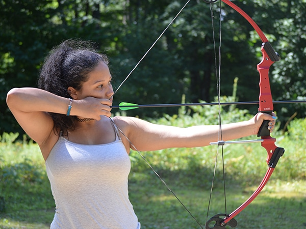 Girl practicing archery at summer camp