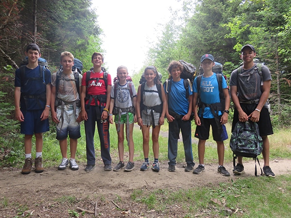 Teens hiking in New England with summer camp counselors