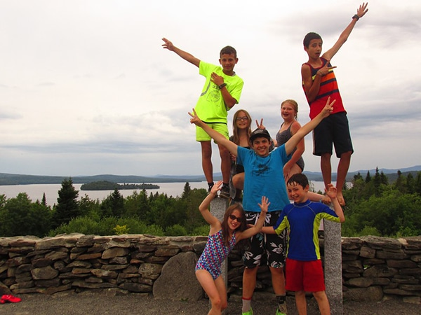 Summer camp kids and teens celebrating reaching the summit of mountain in New England