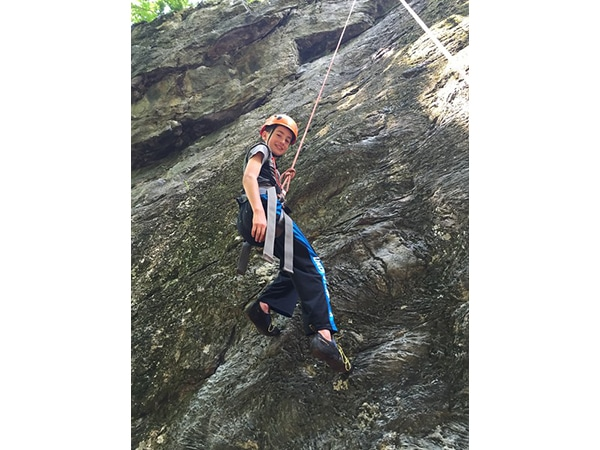 Boy rock climbing in Rumney, New Hampshire with summer camp ropes instructor