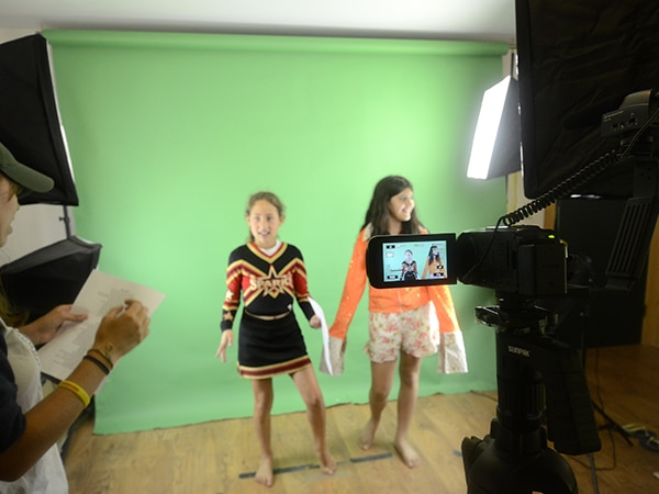Campers in videography class in front of green screen at camp