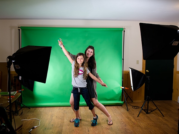 Kids in front of green screen in the videography program at summer camp