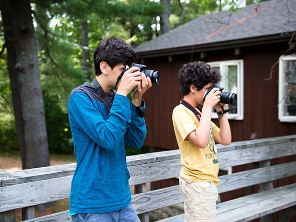 Kids taking photos in the photography program at camp