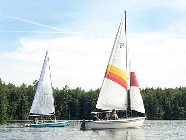 Campers sailing on the lake at Windsor Mountain summer camp in New Hampshire