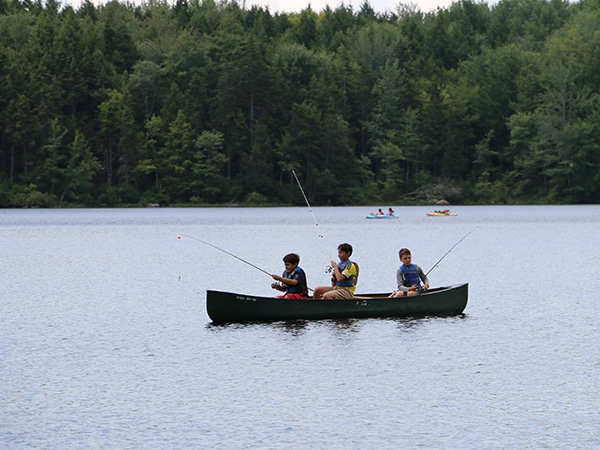 Boys in canoe fishing on lake in New Hampshire