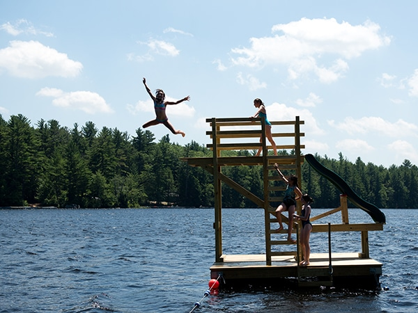 Young girl jumping off dive tower into the lake