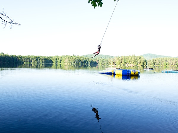 Girl jumping off rope swing into New Hampshire lake