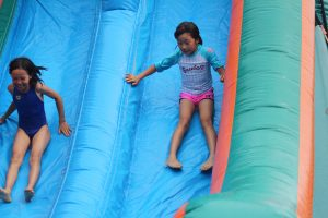 Girls sliding down waterslide at summer camp