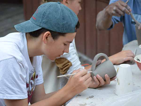 Teen camper making clay mug in the pottery studio at summer camp