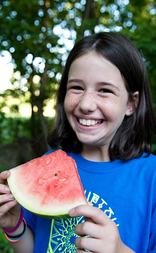 Summer camper enjoying a juicy summer watermelon from the garden