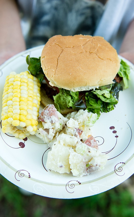 Traditional American summer Barbecue meal with food like burgers, corn on the cob, and potato salad at summer camp