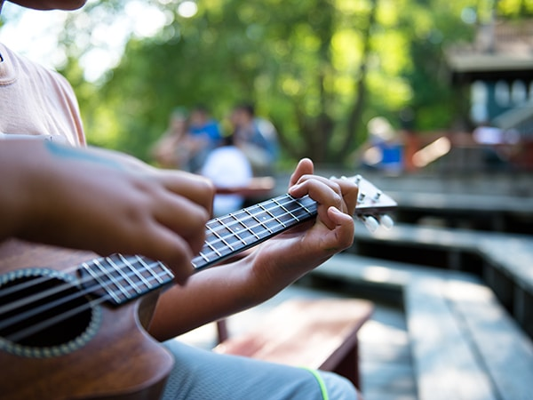 Boy playing ukelele at summer camp