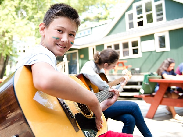 Teen boy playing guitar at summer cam in New Hampshire