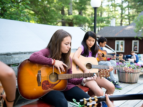 Kids learning guitar during music lessons taught by professional musicians