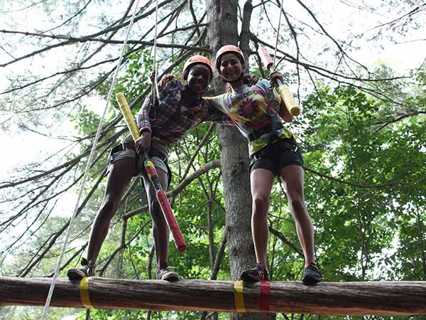 Teen girls challenge on the ropes course at summer camp