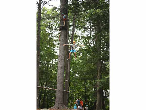 Boy zip lining at summer camp in New Hampshire