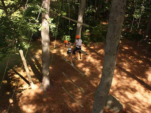 Young female campers climbing Jacob's ladder on the ropes course