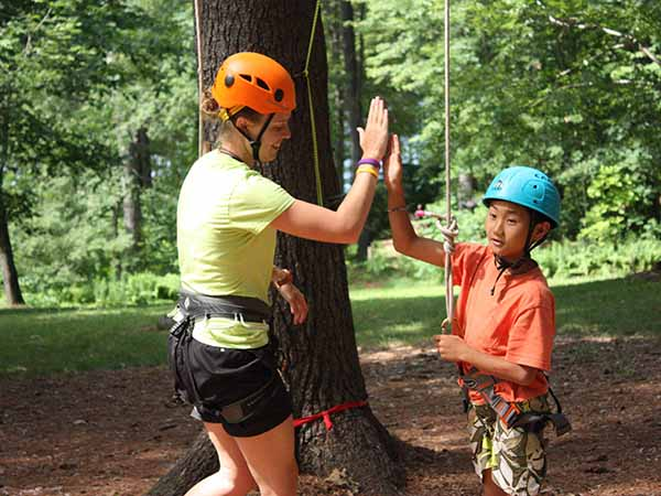 Outdoor climbing instructor congratulates young male camper on the ropes course