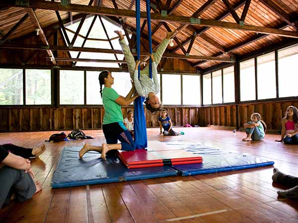Counselor teaching young girl aerial silks at summer camp