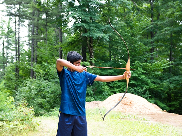 Teen camper practicing archery at new hampshire summer camp