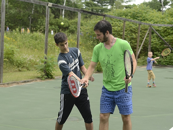 Summer camp counselor teaching tennis techniques to kids at summer camp