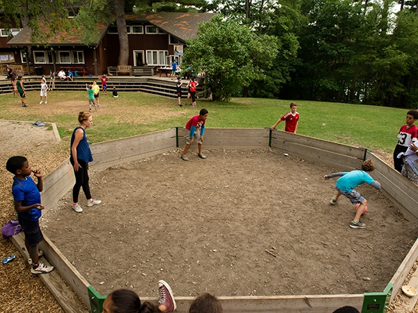 Kids and teens playing gaga ball together at summer camp