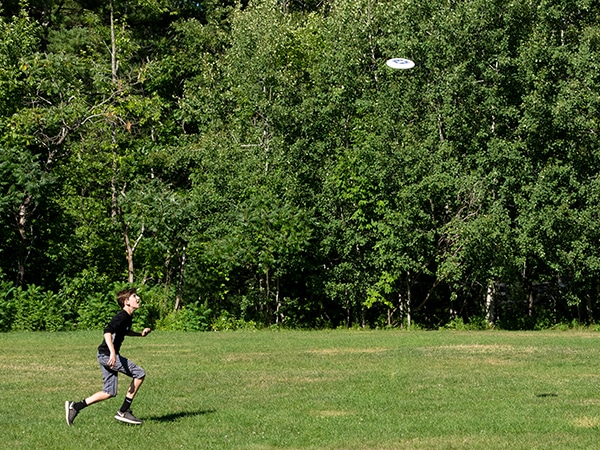 Boy playing frisbee at camp