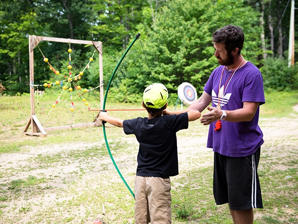 International counselor from New Zealand teaching child archery techniques
